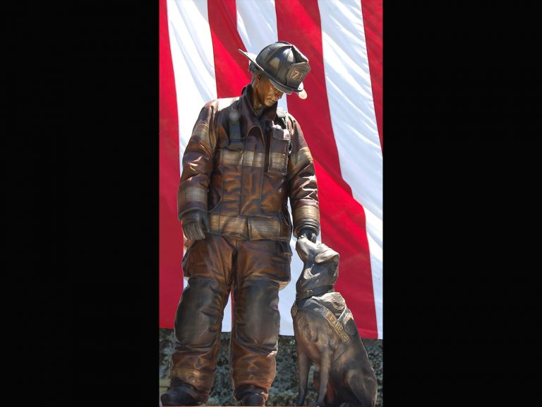 Hnad Sculpted by Austin Weishel, Life size bronze firefighter standing next to his K9 while the unseen bond between handler and k9 is visible